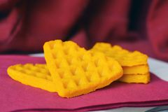 Yellow triangular healthy pumpkin waffle pieces on dark purple background royalty free stock images