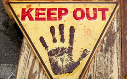 Yellow triangular sign wih keep out in red and an open black hand in stop position. With a wooden background stock image