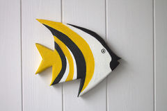Yellow tropical wooden fish on a white background Royalty Free Stock Image