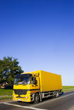 Yellow truck. On asphalt road. Large blue sky with place for copy text royalty free stock photo
