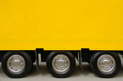 Yellow Truck. Detail of the empty yellow side of a large truck with three wheels Royalty Free Stock Photos