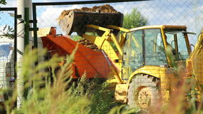 Yellow truck covered with earth in dump. Tractors throws soil in orange body truck. Work on the construction site in the country. Dig the fence stock video footage
