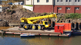 Yellow truck crane. On the water Royalty Free Stock Photography