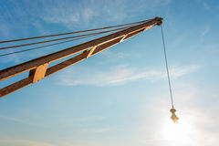 Yellow truck crane boom with hooks and scale weight above blue s Stock Photography