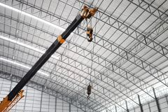 Yellow truck crane boom with hooks in the warehouse. Stock Images