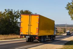 Truck moves on a country road. Yellow truck moves on a country road towards another truck moving towards each other Royalty Free Stock Image