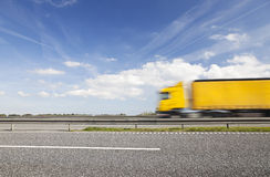 Yellow truck passing by on the highway. Motion blur. Royalty Free Stock Image