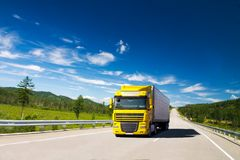 Yellow truck on a road. In a sunny summer day Stock Photo