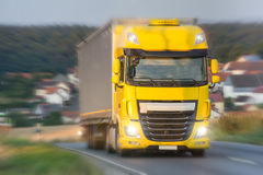 Yellow truck speeding on country road Stock Photography