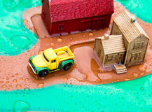 Yellow truck at wet toy farm. Miniature toy truck with house and red barn on wet surface after a rain fall Royalty Free Stock Photography