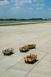 The yellow trucks wait for loading in the platform of airport Stock Images