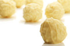 Yellow truffle praline in front of many Stock Photo