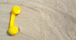 Yellow telephone of an old vintage phone is lying on the sand with a copy space for your text with contacts. stock photo