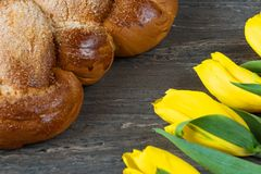Yellow tuips and Easter bread on grey wooden board. Royalty Free Stock Image
