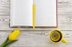 Yellow tulip, cup of tea and notebook Royalty Free Stock Images
