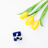 Yellow tulip flowers and ring box on white background. Flat lay, Top view. Stock Photo