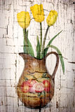 Yellow Tulips. Antiqued yellow tulips in a country vase on cracked paint background Stock Image