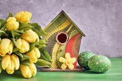 Yellow tulips, birdhouse and painted Easter eggs with decorative Stock Photos
