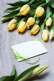 Yellow tulips and a blank greeting card on wooden table Royalty Free Stock Photography