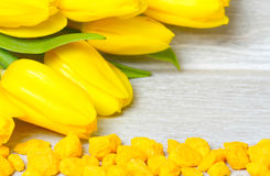 Yellow tulips bouquet and decorative stones on wood Royalty Free Stock Photography