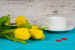 Yellow tulips with coffee cup and two red hearts Stock Photos