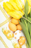 Yellow tulips and colored eggs on the embroidered Royalty Free Stock Images