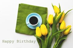 Freshly brewed coffee. Yellow tulips with a cup of coffee on the white table with green cloth, happy birthday sign Stock Photos