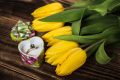 Yellow tulips and engagement ring. On wooden background Stock Images