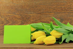 Yellow tulips. With green card on wooden background Stock Photos