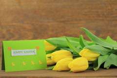 Yellow tulips. With green card on wooden background Royalty Free Stock Image