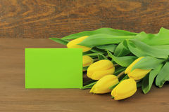 Yellow tulips. With green card on wooden background Royalty Free Stock Photos