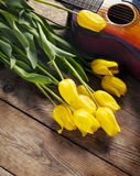 Yellow tulips and guitar on old wood surface. Royalty Free Stock Photo