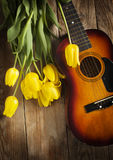 Yellow tulips and guitar on old wood surface. Stock Photo