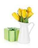 Yellow tulips in a jug and gift box Royalty Free Stock Images