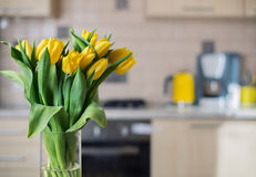 Yellow tulips on kitchen background Royalty Free Stock Photo