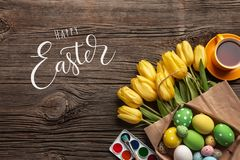 Yellow tulips, a nest with Easter eggs, bright colors and a palette on a wooden background. Top view with copy space royalty free stock photo