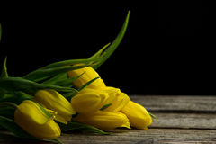 Yellow tulips on old wood table Royalty Free Stock Photos