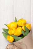 Yellow tulips over wooden table Stock Images