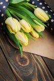Yellow tulips in polka dot kraft envelope Stock Image