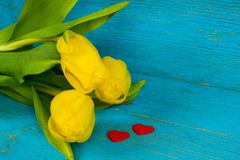 Yellow tulips with two red hearts on turquoise table Royalty Free Stock Photo