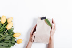 Yellow tulips and woman's hands with gift boxes on a white backg Royalty Free Stock Image