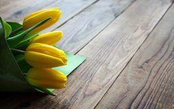 Yellow tulips on a wooden background. A yellow tulips on a wooden background Royalty Free Stock Photos