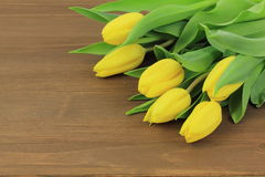 Yellow tulips. On wooden background Royalty Free Stock Photography