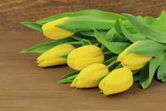Yellow tulips. On wooden background Stock Photo