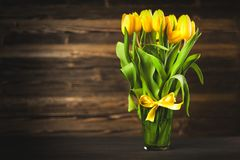 Yellow tulips on wooden background. Yellow tulips in a vase on wood background Royalty Free Stock Photography