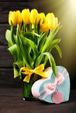 Yellow tulips on wooden background. Yellow tulips in a vase on wood background Royalty Free Stock Image