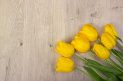 Yellow tulips on a wooden table, easter background Stock Images