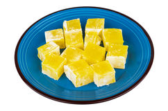 Yellow Turkish delight in blue glass plate isolated on white Stock Image
