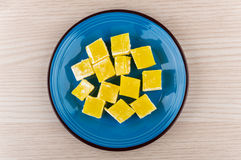 Yellow Turkish delight in blue glass plate on wooden table Stock Image