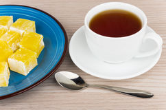Yellow Turkish delight in blue plate and cup of tea Stock Photos